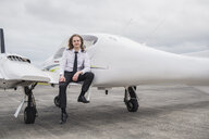 Portrait of smiling male pilot standing on airplane at airport runway against cloudy sky - CAVF62054