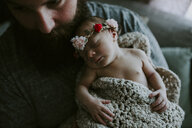 High angle close-up of bearded father carrying cute sleeping daughter wearing tiara while sitting on sofa at home - CAVF62084