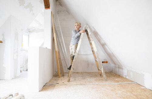 Deutschland, NRW, Haus, Baustelle, Dach, Dachboden, Holz, Leiter, Dachausbau, Dachschraege, Junge steht auf Holzleiter - MFRF01167