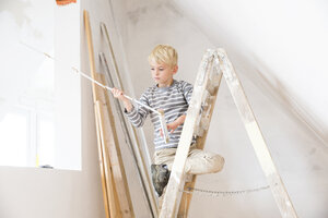 Boy with pocket rule on ladder in attic to be renovated - MFRF01170