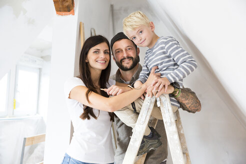 Portrait of happy family working on loft conversion - MFRF01179