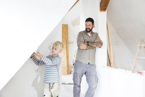 Deutschland, NRW, Haus, Baustelle, Dach, Dachboden, Holz, Dachausbau, Dachschraege, Junge misst Wand mit Wasserwaage aus, Vater, Sohn - MFRF01182