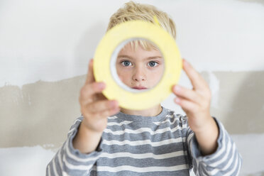 Portrait of boy looking through sticky tape toll - MFRF01191