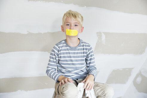 Deutschland, NRW, Haus, Baustelle, Dach, Dachboden, Holz, Dachausbau, Dachschraege, Portrait, Junge sitzt auf Leiter mit einem Stueck Klebeband auf dem Mund - MFRF01194