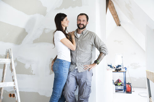 Portrait of confident couple standing in attic to be renovated - MFRF01197