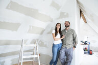 Confident couple standing in attic to be renovated looking up - MFRF01200