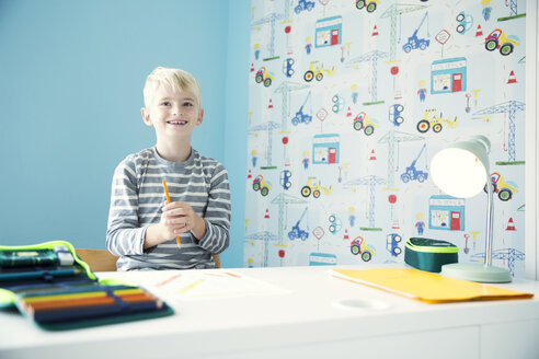 Smiling boy doing homework at desk in children's room - MFRF01221