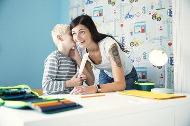 Mother helping son doing homework at desk - MFRF01224
