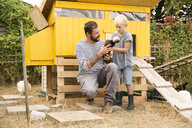Father and son with Polish chickens at chickenhouse in garden - MFRF01245
