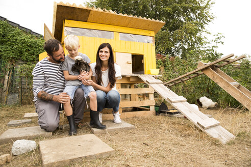 Portrait of happy family with Polish chicken at chickenhouse in garden - MFRF01251