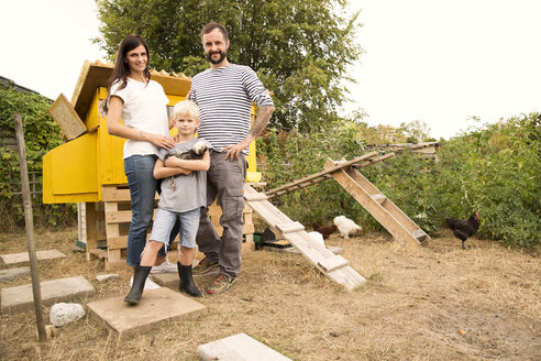 Portrait of confident family with Polish chicken at chickenhouse in garden - MFRF01254