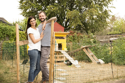 Portrait of confident couple standing at chickenhouse in garden - MFRF01266