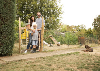 Portrait of confident family standing at chickenhouse in garden - MFRF01269