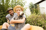 Father with son sitting in wheelbarrow holding chicken - MFRF01275