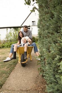 Deutschland, NRW, Garten, Haus, Portrait, Frau und Junge sitzten in Schubkarre und werden von Mann geschoben - MFRF01278