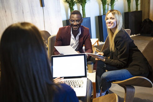 Business people sitting in a hotel lobby, working together - JSRF00167