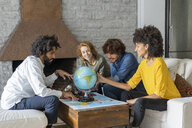 Friends meeting to plan vacations, checking map and globe - AFVF02515