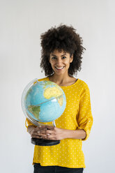 Beautiful woman holding globe, planning vacations - AFVF02542