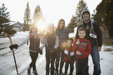 Portrait smiling family with ice hockey sticks and ice skates on snowy road - HEROF26299