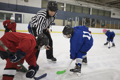 Referee dropping puck for boy ice hockey players at face off on ice hockey rink - HEROF26302