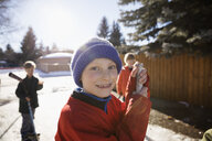 Portrait smiling boy playing ice hockey in sunny, snowy driveway - HEROF26305