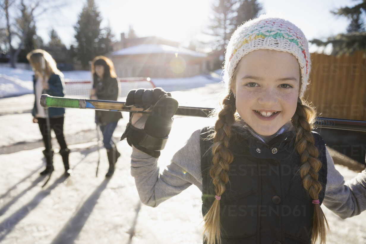 Portrait smiling, confident girl playing ice hockey in sunny, snowy driveway - HEROF26308 - Hero Images/Westend61