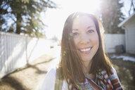 Portrait smiling brunette woman on sunny road - HEROF26317