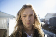Portrait serious, confident young man with long blonde hair on sunny road - HEROF26320