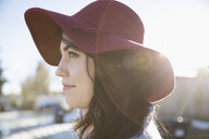 Profile portrait young brunette woman in red fedora on sunny road - HEROF26332