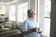 Senior man drinking coffee and looking out window in beach house - HEROF26383