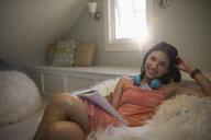 Portrait smiling teenage girl with headphones writing in notebook in fuzzy bean bag chair - HEROF26413