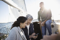 Senior friends texting with cell phone on sunny sailboat - HEROF26437