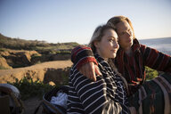 Serene, affectionate young couple on sunny beach rocks - HEROF26461
