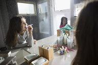 Sisters brushing teeth in bathroom mirror - HEROF26464