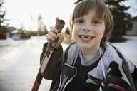 Portrait enthusiastic gap toothed boy holding ice hockey stick and ice skates on snowy road - HEROF26491
