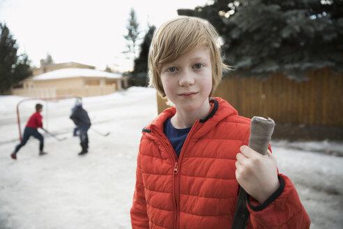 Portrait confident boy playing ice hockey in snowy driveway - HEROF26494
