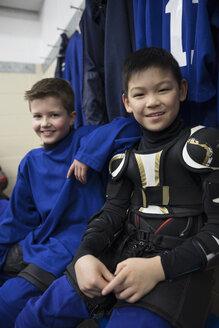 Portrait confident boy ice hockey players in protective sportswear in locker room - HEROF26497