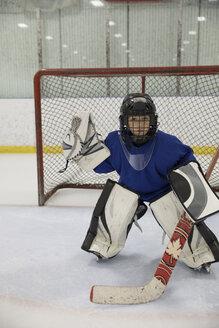 Portrait focused boy ice hockey goalie player at net on ice - HEROF26503