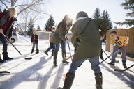 Mothers and sons playing ice hockey in sunny, snowy driveway - HEROF26515