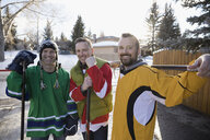 Portrait confident men playing ice hockey in driveway - HEROF26521