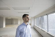 Pensive businessman at window in empty highrise open plan office - HEROF26584