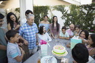 Multi-generation family celebrating birthday with cake and gifts on patio - HEROF26623