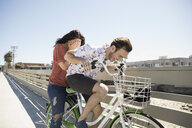 Playful couple laughing on bicycle on sunny bridge - HEROF26665