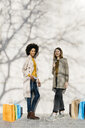 Portrait of two happy women with shopping bags standing at a wall - JRFF02764