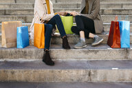 Two women with shopping bags sitting on stairs checking the purchase - JRFF02770