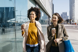 Two happy women with shopping bags and takeaway coffee walking in the city - JRFF02773