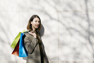 Portrait of smiling woman with shopping bags standing at a wall - JRFF02782
