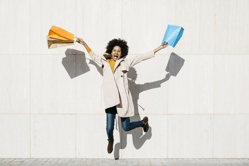 Cheerful woman with shopping bags jumping at a wall - JRFF02785