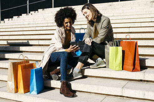 Two happy women with shopping bags sitting on stairs using cell phone - JRFF02788
