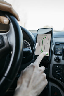 Close-up of woman driving in a car using a telephone navigation app - JRFF02797